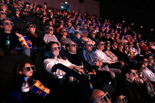 An audience at a movie wearing modern 3D cross polarization glasses.