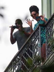 Jay-Z snaps photos while Beyonce waves to fans from the balcony of their room at Saratoga Hotel in Havana, Cuba.