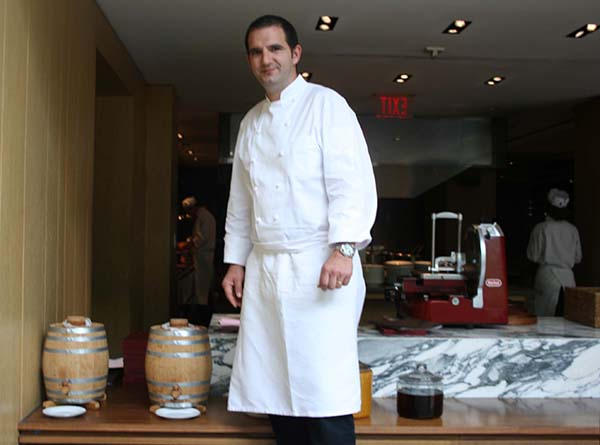 Blue Duck Tavern Executive Chef Sebastien Archambault stands beside the two barrels of house-made vinegar on display in front of the open kitchen. (Mark Heckathorn/DC on Heels)