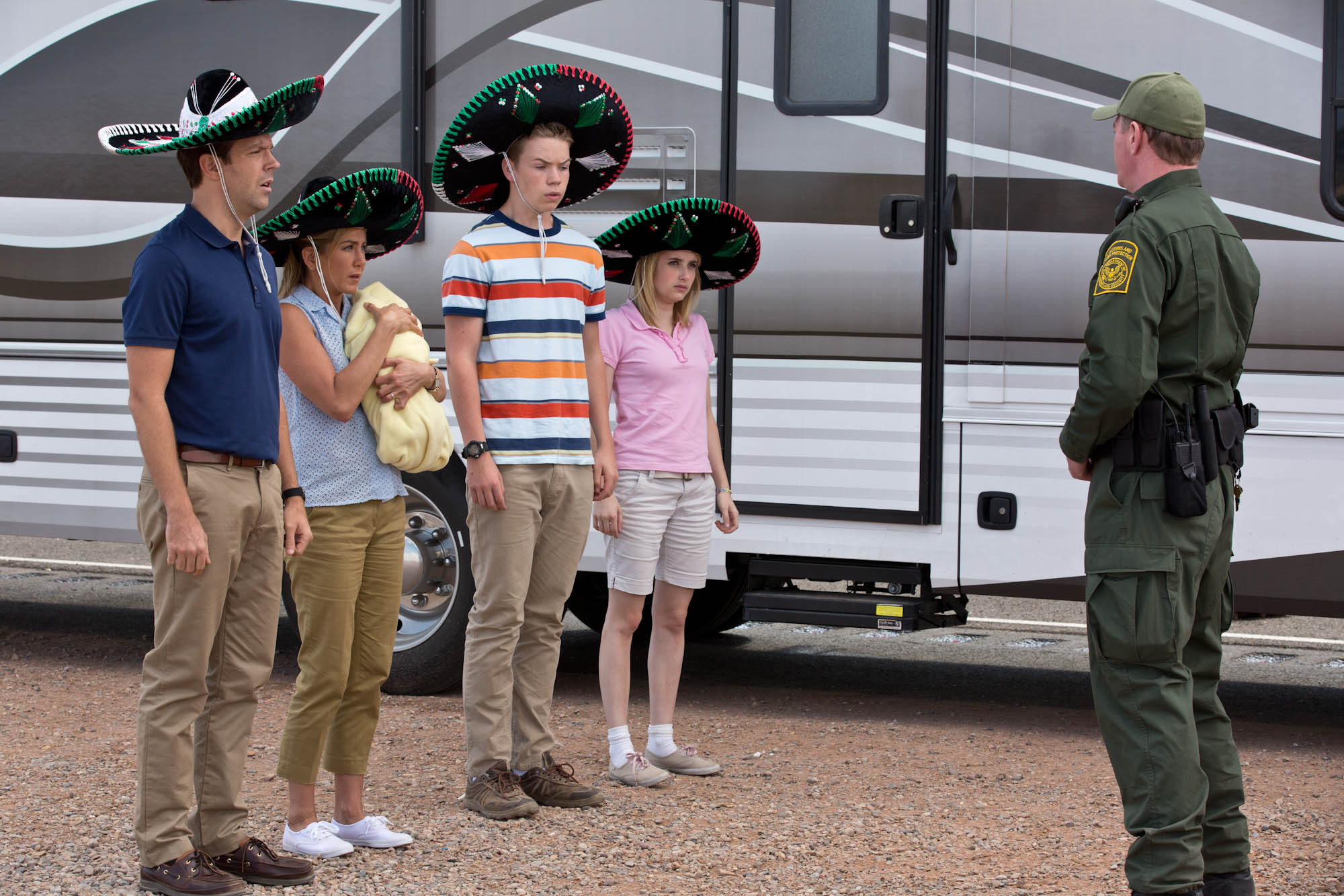 The Millers (Jason Sudekis, Jennifer Aniston, Will Porter and Emma Roberts) attempt to pass through Customs at the U.S.-Mexican border. (Photo courtesy of Warner Bros. Pictures)