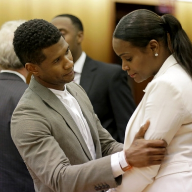 R&B singer Usher, left, embraces ex-wife Tameka Foster Raymond, after a judge dismissed an emergency request by Raymond seeking temporary custody of their two children, Friday in Atlanta. Raymond had requested the hearing earlier this week after their 5-year-old son got caught in a pool drain while in the care of the Grammy winner's aunt. (David Goldman/AP)