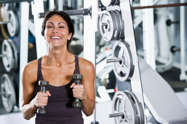 Woman lifting weights in a gym. (Photo: sheknows.ca)