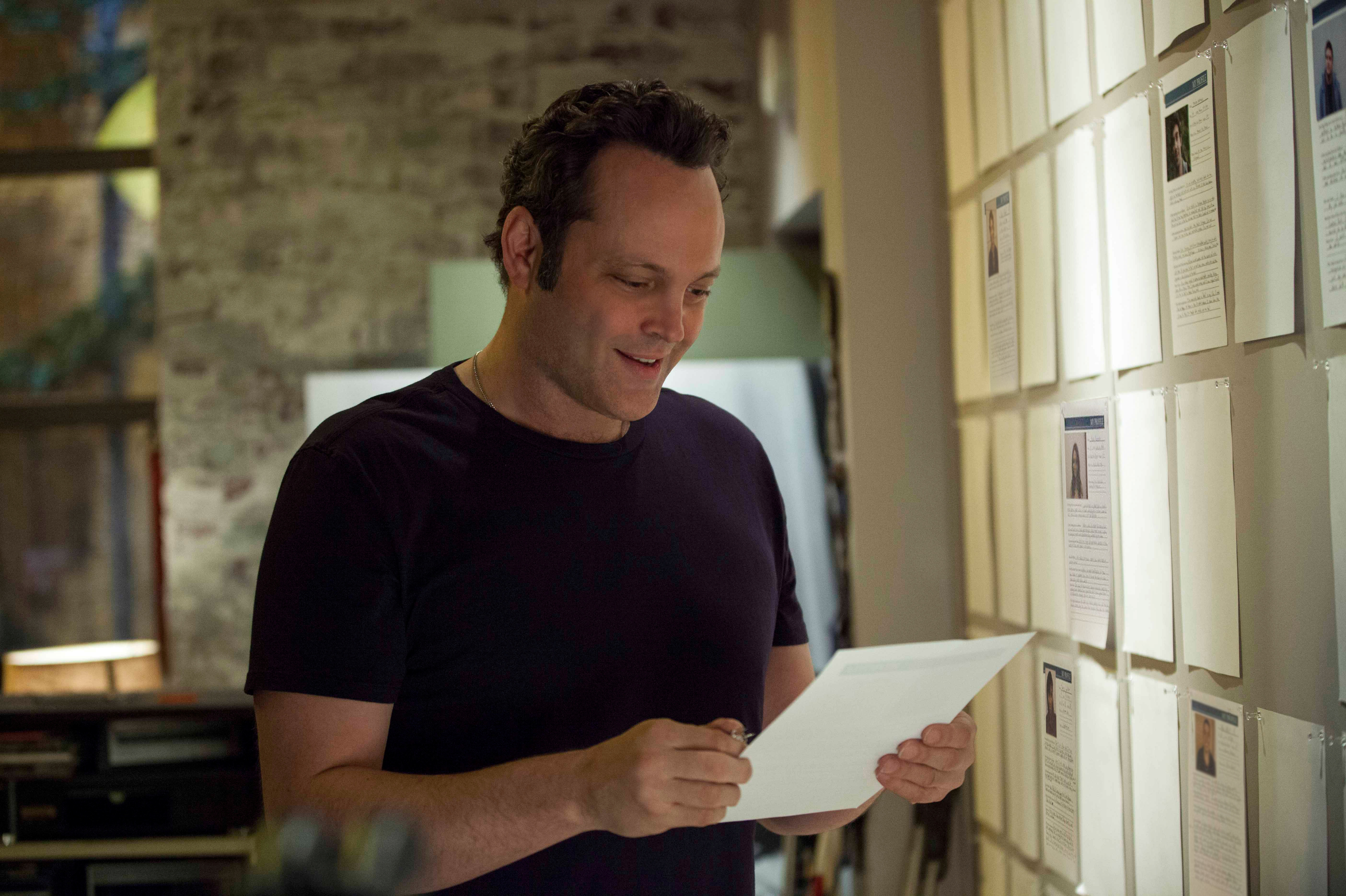 David Wozniak (Vince Vaughn) looks at profiles of some of the 533 kids he has sired. (Photo: Dreamworks Pictures)