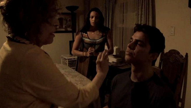 Jesse's grandmother (Renee Victor) performs an exorcism on her grandson (Andrew Jacobs) as his friend Marisol (Gabrielle Walsh) watches in Paranormal Activity: The Marked Ones. (Photo: Paramount Pictures)