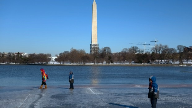 Children slide along an ice-covered walkway near the Washington Monument Saturday. But with the polar vortex coming Monday and Tuesday you should stay inside or dress warmly if you must go out. (Photo: Karen Bleier/AFP/Getty Images)