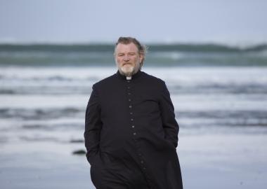 Father James (Brandon Gleeson) walks along an Irish beach were a parishioner plans to kill him for sins of a long-dead priest in