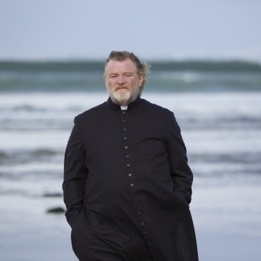 Father James (Brandon Gleeson) walks along an Irish beach were a parishioner plans to kill him for sins of a long-dead priest in