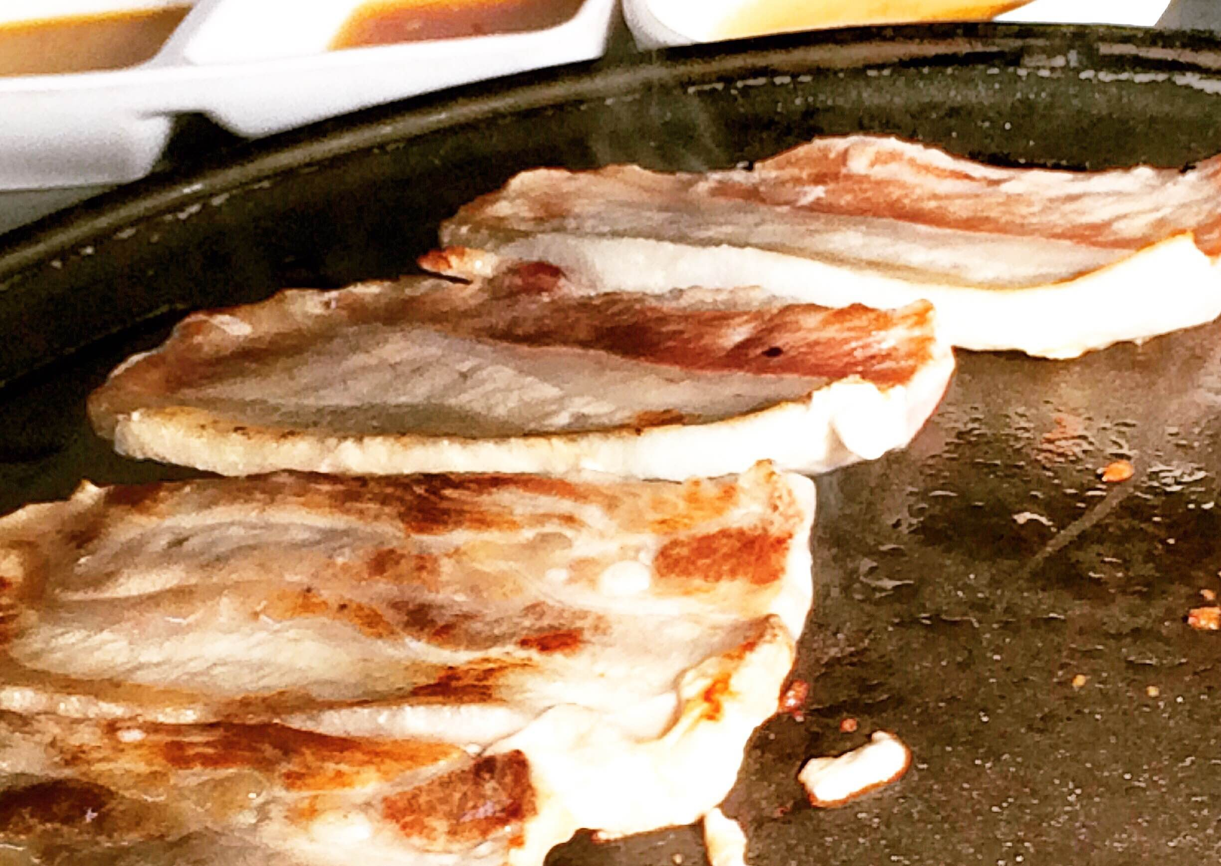 Pork belly cooking on the grill in the center of the table. (Photo: Diana Veseth-Nelson/DC on Heels)