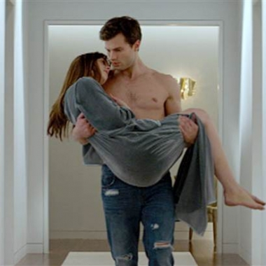 Christian Grey (Jamie Dornan) carries Anastasia Steele (Dakota Johnson) in Fifty Shades of Grey.