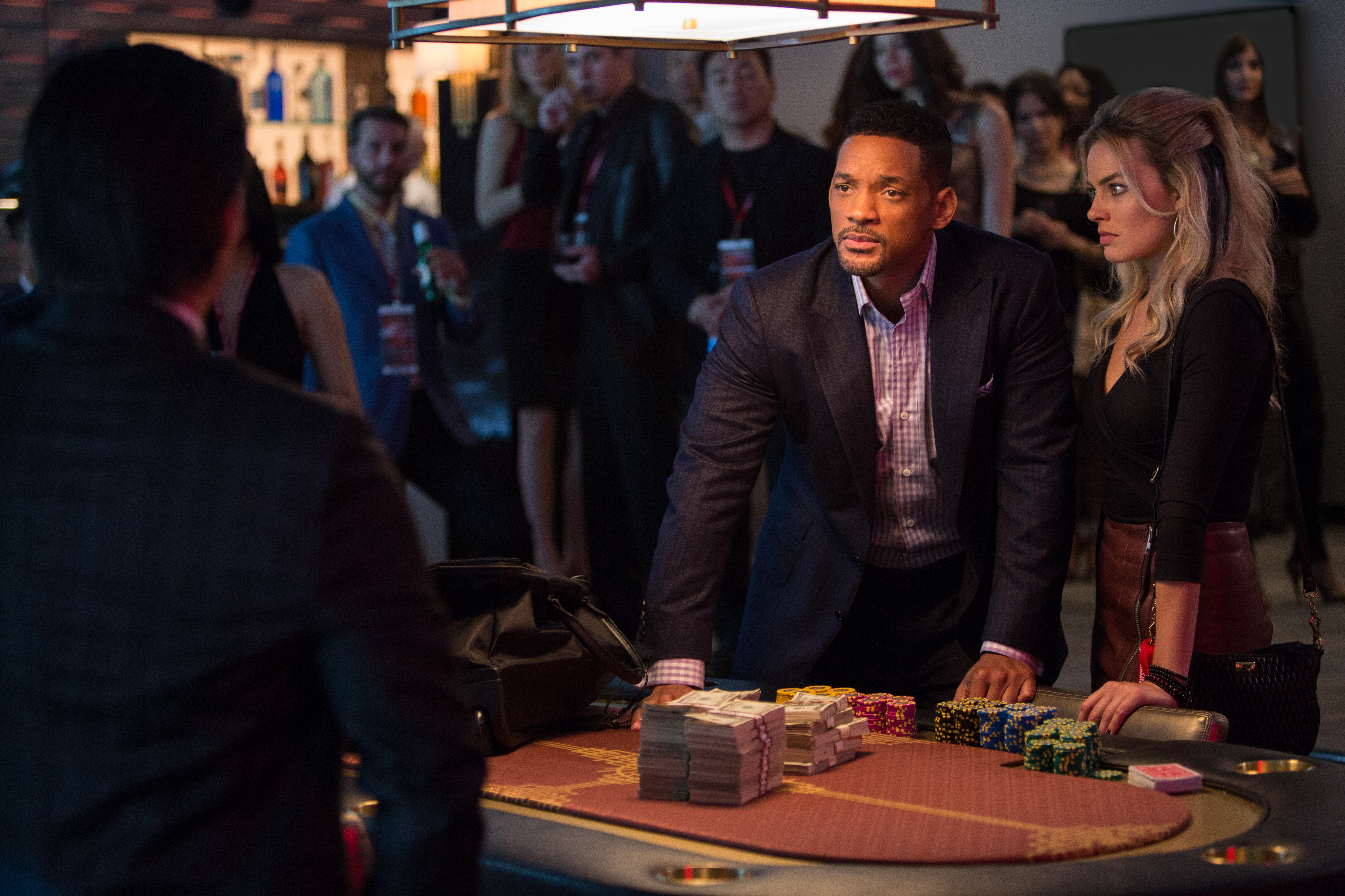 "Nicky Spurgeon (Will Smith, left) is an extremely accomplished con man who takes an amateur con artist, Jess (Margot Robbie), under his wing in ""Focus"". (Photo: Warner Bros. Pictures)"