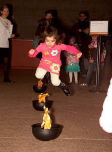 A child jumps over a faux fire at last year's Nowruz Festival. (Photo: Smithsonian Institution)