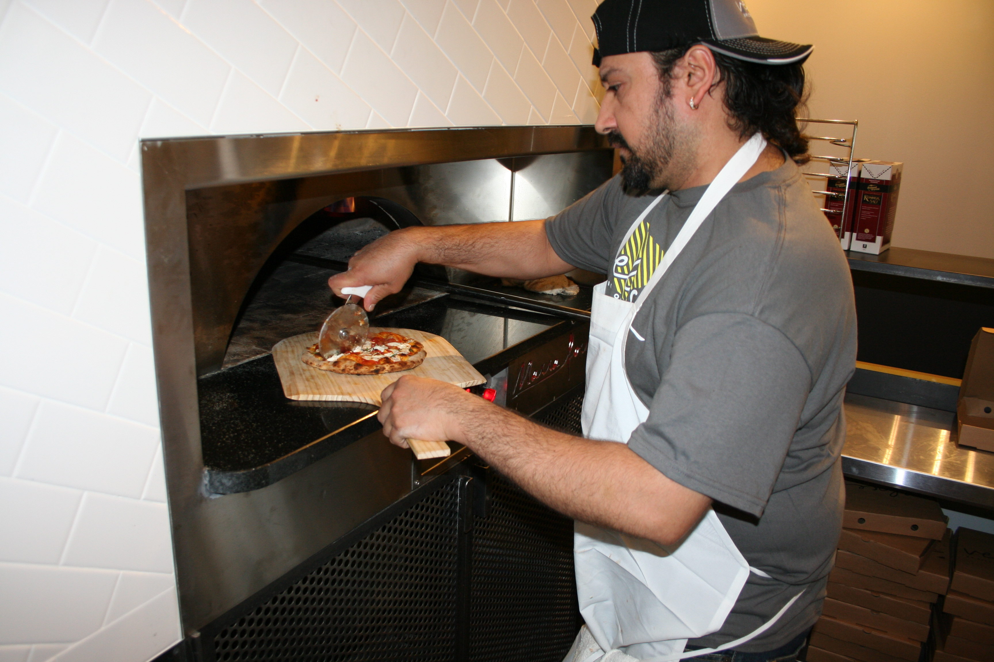 An employee removes a personal pizza from Veloce's specially-made gas oven. (Photo: Mark Heckathorn/DC on Heels)