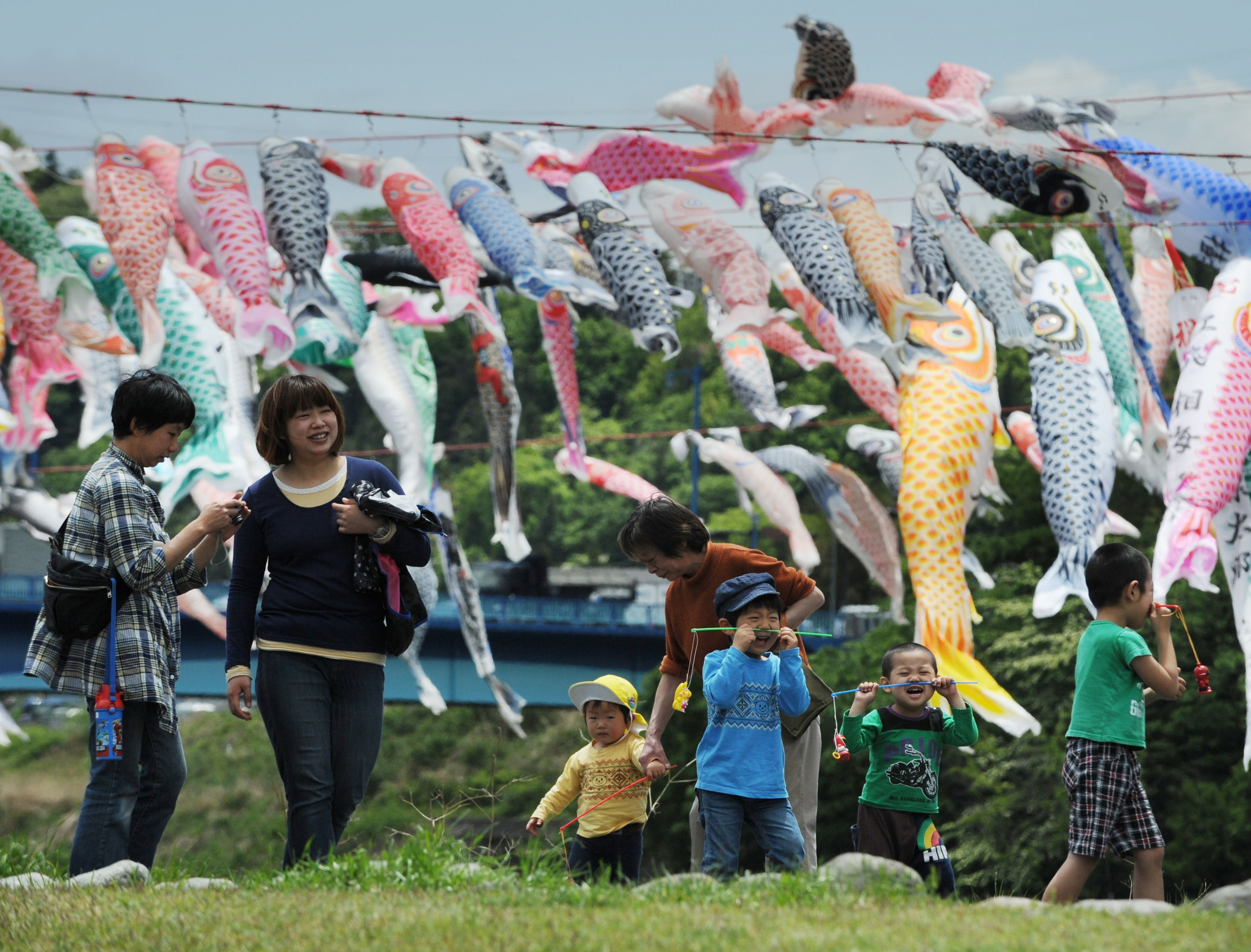 A family walks beside colourful carp streamers flying above a riverside park in Sagamihara, Kanagawa prefecture, Japan, in celebration of Children's Day. (Photo: AFP)A family walks beside colourful carp streamers flying above a riverside park in Sagamihara, Kanagawa prefecture, Japan, in celebration of Children's Day. (Photo: AFP)