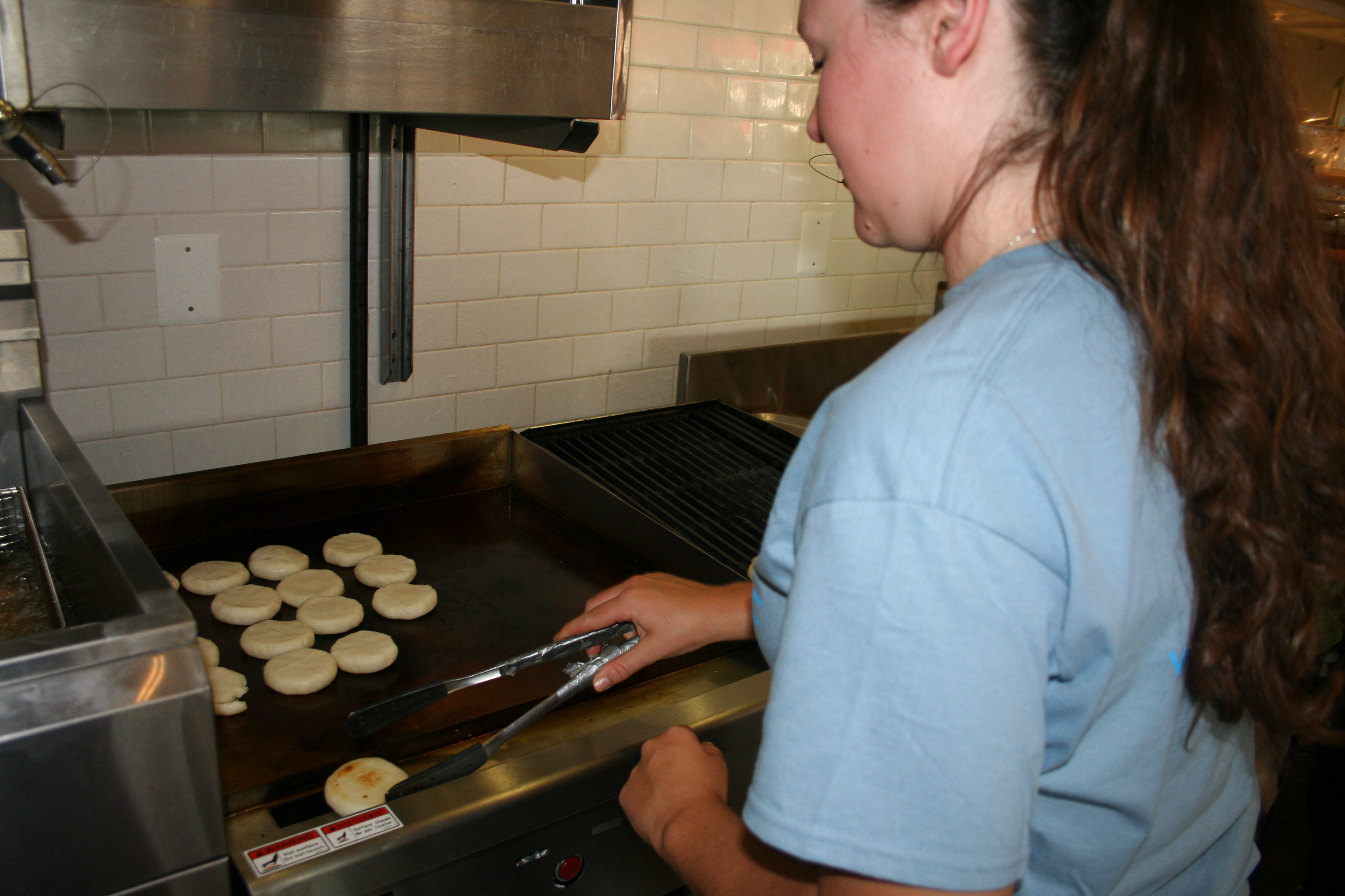 An employee grills the arepas before they are filled. (Photo: Mark Heckathorn/DC on Heels)
