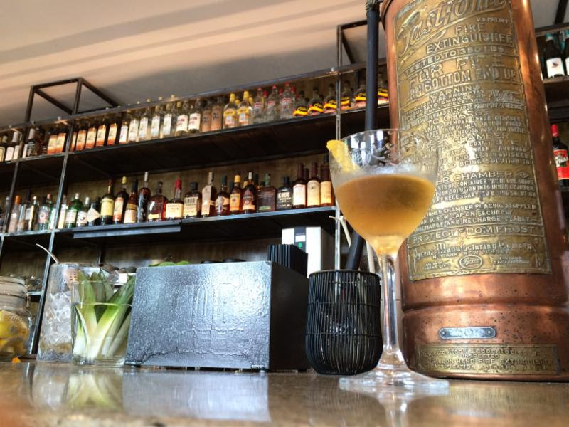 The Royal's happy hour specials include housemade vermouth from a vintage copper fire extinguisher. (Photo: The Royal)