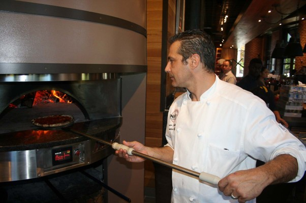 Chef Mauro Molino takes a pizza out of Lena's Wood-Fired Pizza & Tap's custom made, wood-burning oven. (Photo: Mark Heckathorn/DC on Heels)Chef Mauro Molino takes a pizza out of Lena's Wood-Fired Pizza & Tap's custom made, wood-burning oven. (Photo: Mark Heckathorn/DC on Heels)
