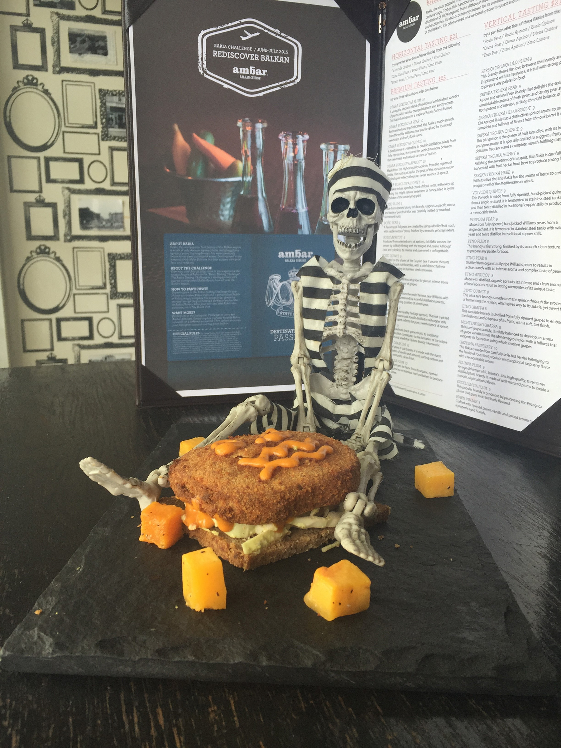 Ambar will feature a Halloween-themed sandwich  with organic slaw mix, breaded smoked gouda cheese, ajvar emulsion and roasted pumpkin cubes on gluten free bread topped shaped and decorated with the face of a jack-o-lantern from Oct. 26-Nov. 1. (Photo: Ambar)