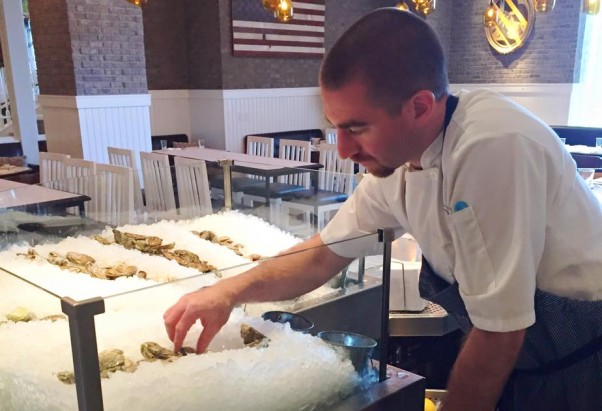 An employee fills the oyster bar at America Eats Tavern. (Photo: America Eats Tavern/Facebook)