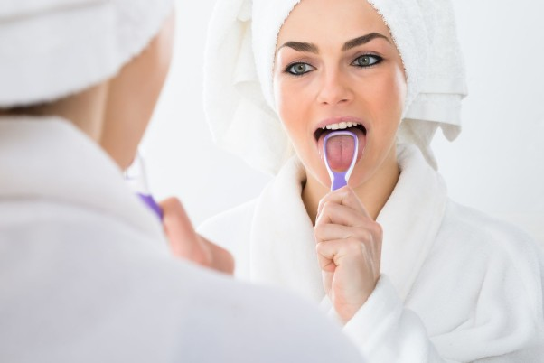 Use a tongue scraper along with brushing to get rid of germs on your tongue that cause bad breath. (Photo: Deposit Photos)