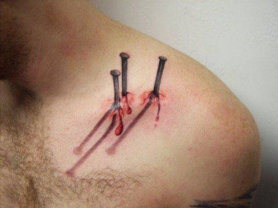 A realistic looking tattoo of nails driven into a shoulder. (Photo: Buzzy Tube)
