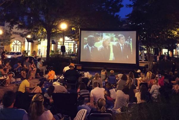 People sitting in the grass watch a movie on a big outdoor screen on The Loop at Market Common Clarendon. (Photo: Market Common Clarendon)