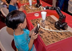 A visitor to Mars Day collects wooden blocks with a robotic arm. (Photo: National Air and Space Museum)