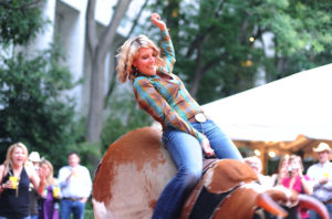 Megan Degenfelder, from the office of Rep. Cynthia Lummis, R-Wyo., rides a mechanical bull at COWPIE. (Photo: CQ Roll Call)