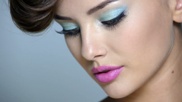Break out lighter colored eyeshadows like aqua with coral lipstick. (Photo: Videezy)