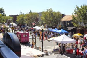 Food trucks and booths with people browsing along 8th Street SE. (Photo: Barracks Row Main Street)