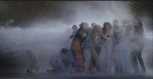 "A group of people being sprayed with powerful hose of water from ""The Raft"" by Bill Viola, a  high-definition color video. (Photo: Bill Viola Studio)"