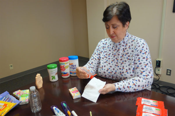 Donna Duberg, assistant professor of biomedical science at Saint Louis University, prepares surface wipes by squirting hand sanitizer on a tissue, as part of her germ-fighting travel kit. (Photo: Ellen Hutti)