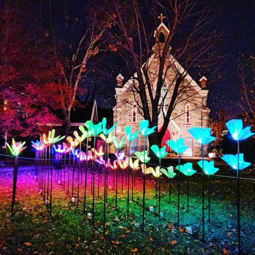 """On the Wings of Freedom"" by Aether & Hemera on Grace Church's lawn depicts butterflies, the symbol of change, creativity, soul freedom, joy and color. A kaleidoscope of glowing butterflies, the installation is made of dozens of origami encasing colored and dynamic LEDs. (Photo: travelsofadam/Instagram)"