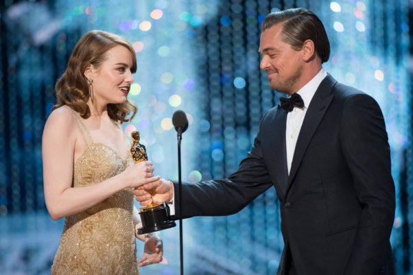 Emma Stone accepts her Oscar for Performance by an actress in a leading role, for work on <em>La La Land</em> from Leonardo DiCaprio. (Photo: Aaron Poole/A.M.P.A.S.)