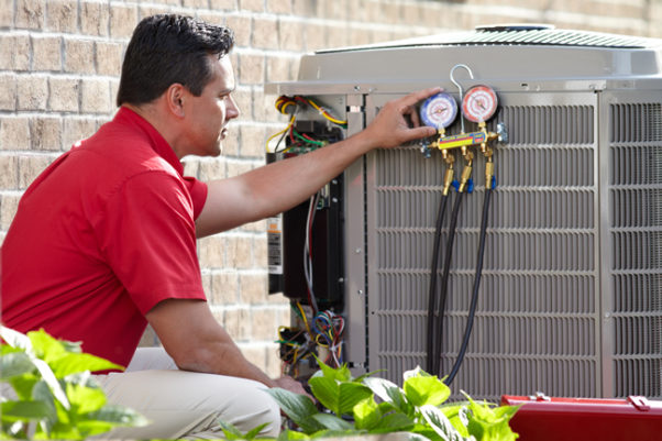 Repairman checking guages on central air conditioning unit.