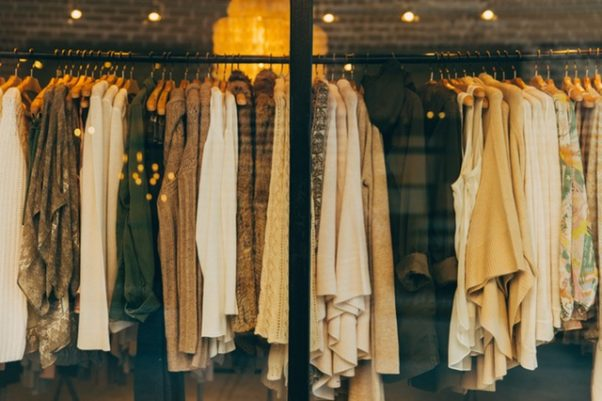 clothing hanging on a rack in a closet (Photo; tookapic/Pexels)
