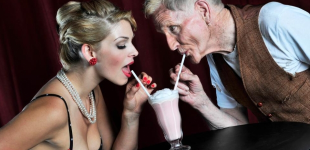 Younger woman and older man sharing a milk shake. Photo: Getty Images