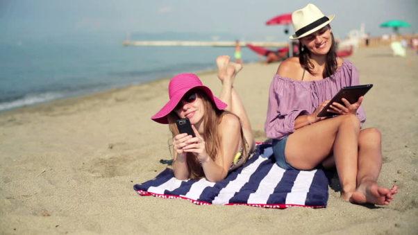 two women lying on the beach. (Photo: Shutterstock)