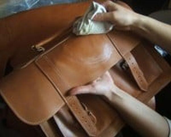 person rubbing oil onto a messenger bag with a cloth (Photo; Bidinis Handbags)