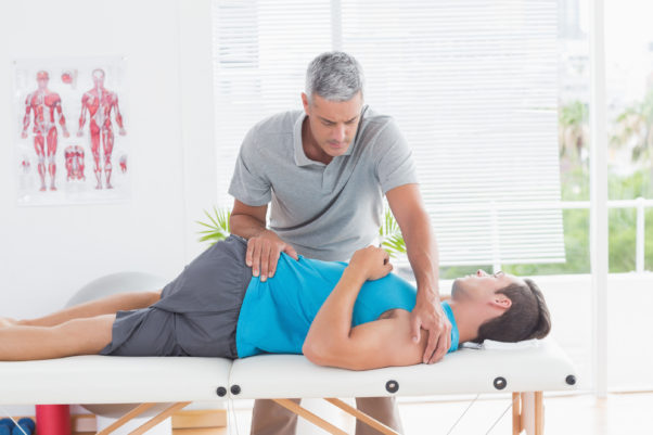 Doctor stretching a young man back in medical office. (Photo: Bigstock)