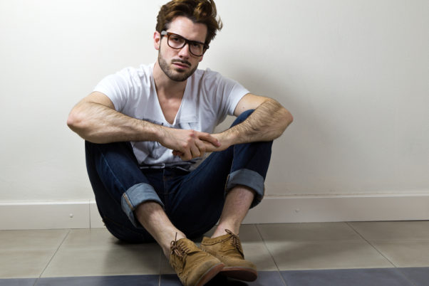 male model sitting on floor in tshirt and jeans. (Photo: Shutterstock)