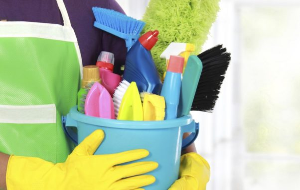 Portrait of person with a bucket full of cleaning suppies (Photo: Getty Images)