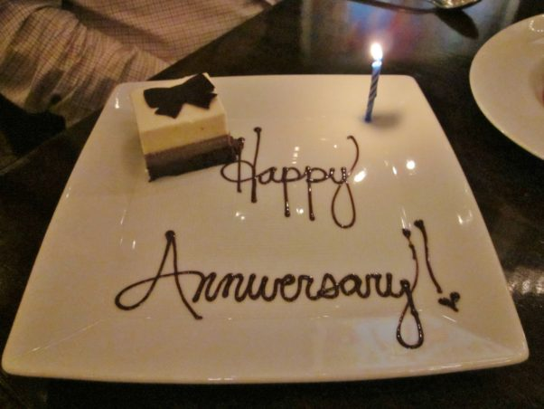 Plate that says happy anniversary on it with cake and candle on it. (Photo: HD Wallpapers)