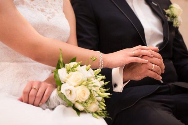 closeup of bride and groom holding hands (Photo: debowscyfoto/Pixabay)