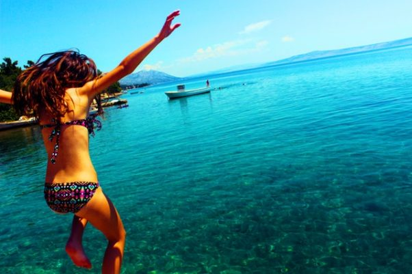 woman in bikini jumping into crystal blue water (Photo: Isabelle Bruce/Pexels)