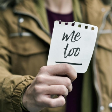 Woman holding piece of note paper that says Me Too (Photo:
