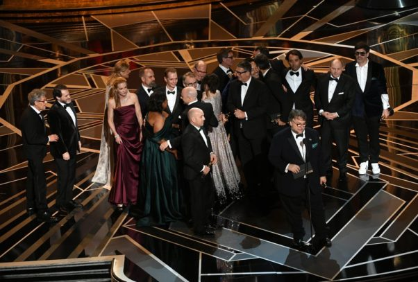 Guillermo del Toro, at the microphone, accepts the Best Picture Oscar for <em>The Shape of Water</em> with the cast and crew behind him. (Photo: Getty Imaages)
