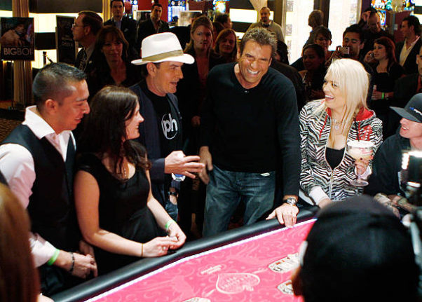 Reporter Jerry Penacoli and Charlie Sheen (center) play a table game as Sheen hosts an evening at Planet Hollywood Resort & Casino. (Photo: Isaac Brekken/Getty Images)