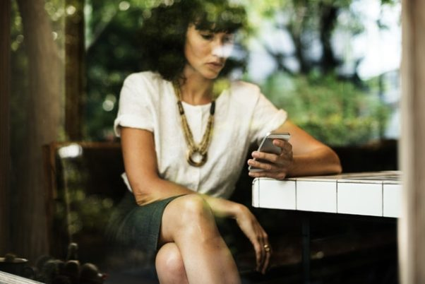 Woman sitting at table in window texting wiht bust-length statement necklace. (Photo: rawpixels/Pexels)
