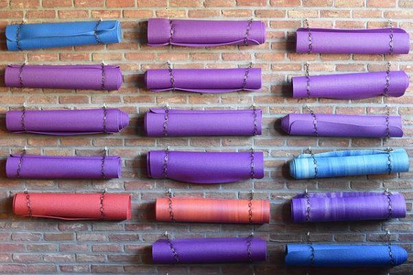 several yoga matts hanging in three rows on the wall (Photo: Ben_Kerckx/Pixabay)
