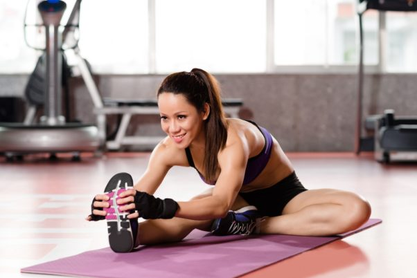 A woman stretching in the gym. (Photo: Deposit Photos)